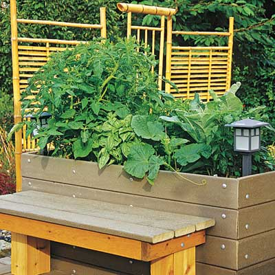 a raised garden bed with a bench in front