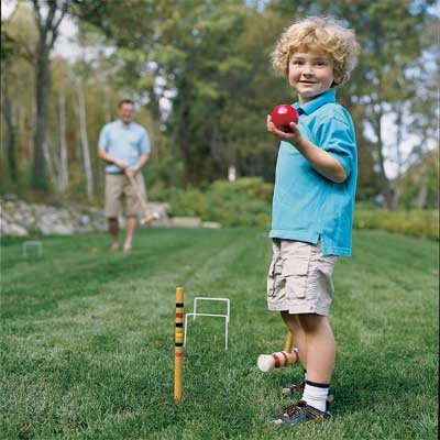 child playing croquet game in yard