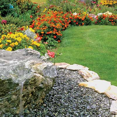 a flowery, colorful garden in late summer with stone edging