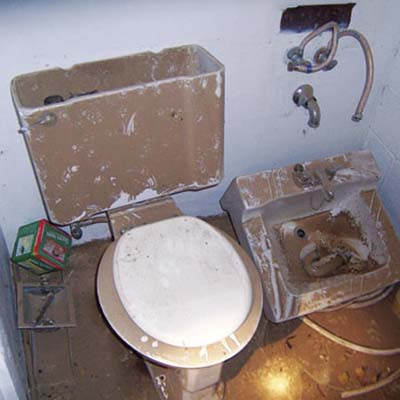 dirty dusty bathroom with with broken toilet and sink