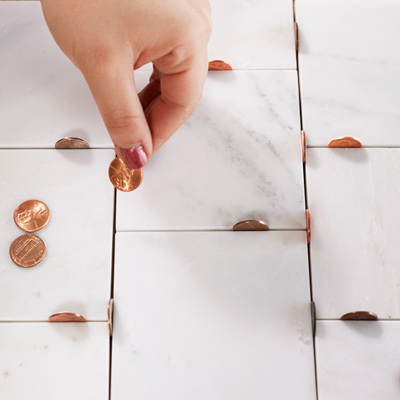 pennies on end between tiles