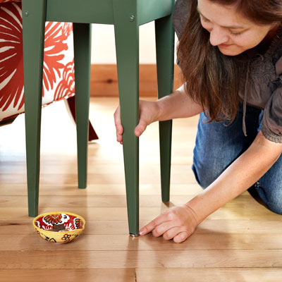 woman putting a penny under a shaky table leg