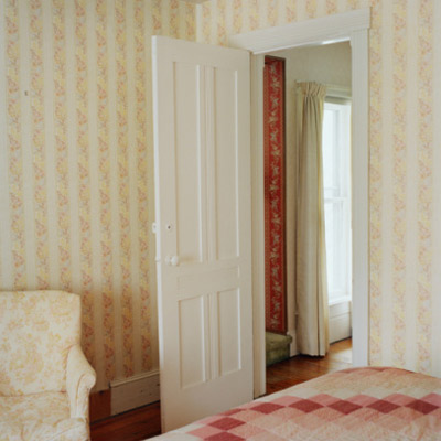 bedroom with an open door and yellow and white wallpaper