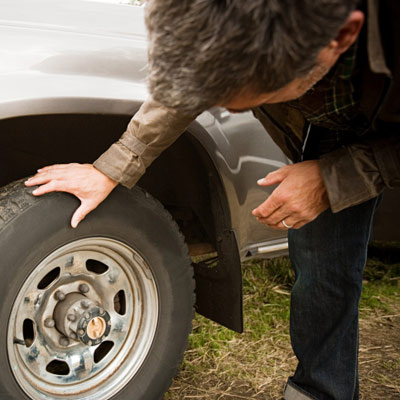 man checking his car tires