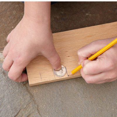 person using a quarter to measure an inch
