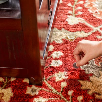 person using a coin to fluff carpet