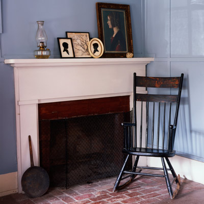 vintage rocking chair on brick hearth floor with fireplace mantel