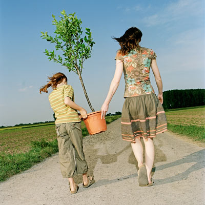 woman and child carrying sapling tree