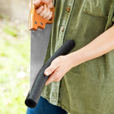 woman sliding pipe insulation on teeth of handsaw