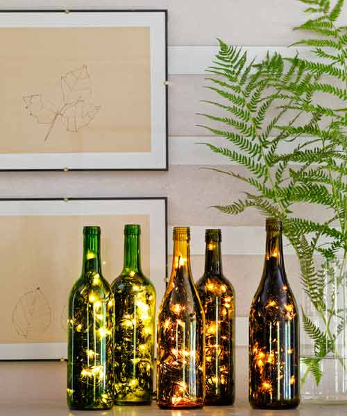 empty wine bottles with string lights in them for holiday decorations