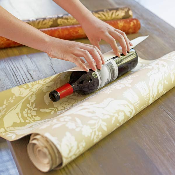 Using an empty wine bottle as a spool to roll kinks out of wallpaper