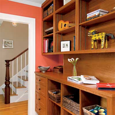 a warm shade of paint adds personality for this home office upgrade with built-in bookshelves, powder room, and desk area