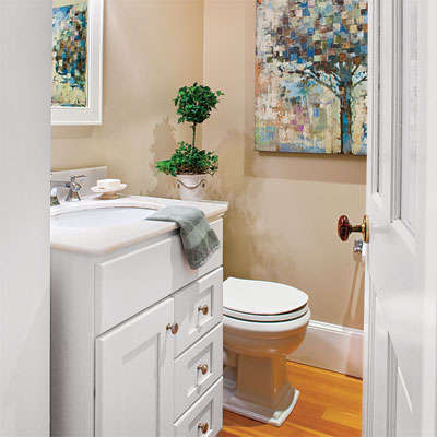 a small powder room was added to this home office upgrade with built-in bookshelves, powder room, and desk area