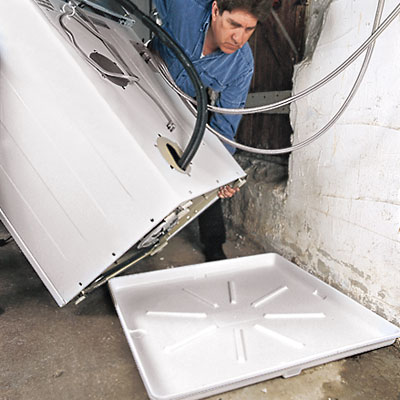 worker moves a washer onto a washer drain pan