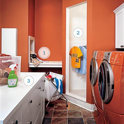 a laundry room with red walls, laundry chute, shower stall and island