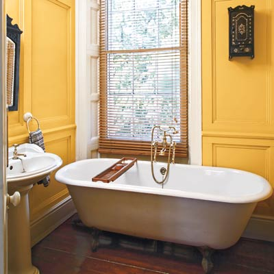 bathroom with a soaking tub and a yellow wall