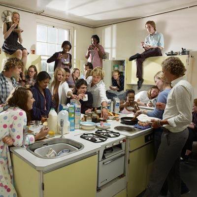 a large group of people in kitchen eating and talking