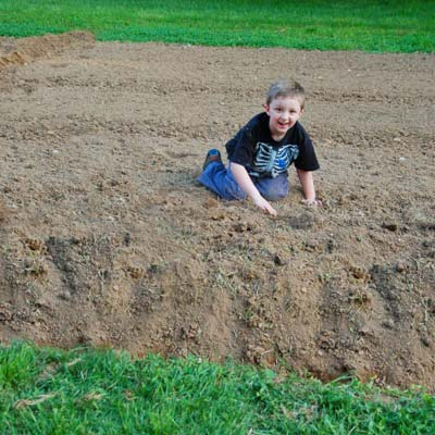 little boy sitting on patch of dirt in yard