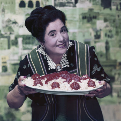 woman holding large plate of spaghetti and meatballs