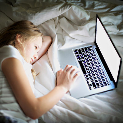 girl on laptop in the dark in her bed