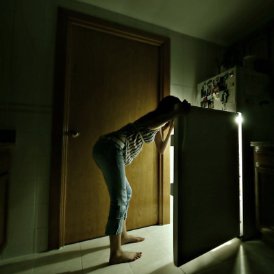 woman looking in fridge for snack in a dark kitchen