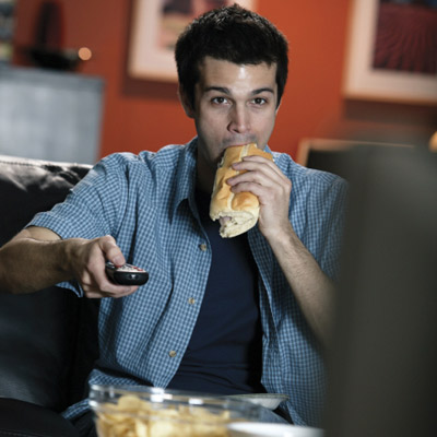 man eating a sandwich while he watches TV
