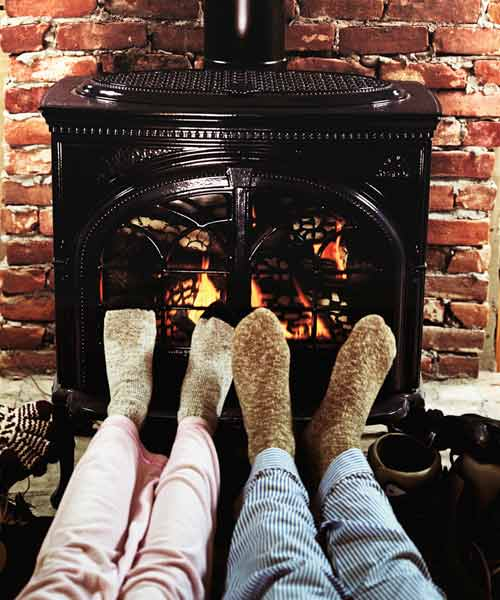 two people warming feet in front of pellet stove