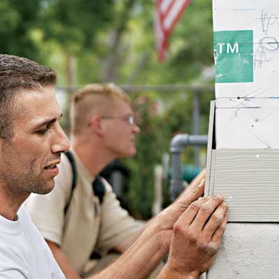construction workers installing fiber cement siding