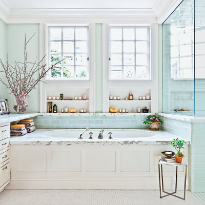 blue and white master bath with a marble-framed tub