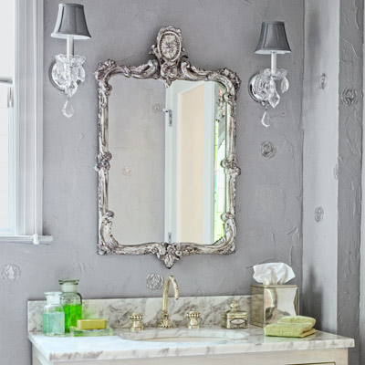 1930s Hollywood Regency-style bath with marble-topped vanity, silver-leaf vanity mirror and crystal sconces