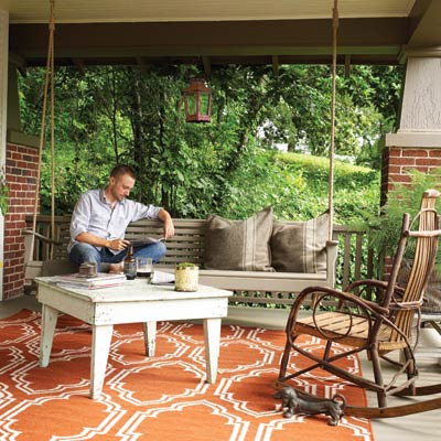a porch with porch swing, outdoor furniture and area rug, man sits reading on the porch swing