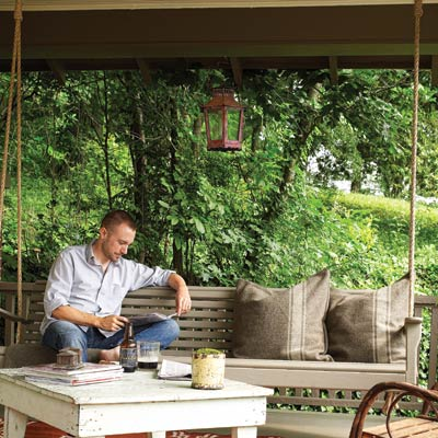 man sits reading on a porch swing