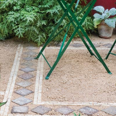 a patio with pea-gravel surface and paver tile edging