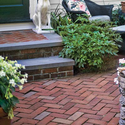 a patio outside a front entry with a herringbone-patterned brick path