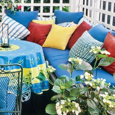 a deck with outdoor cushions and throw pillows