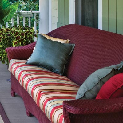 a porch with a wicker loveseat