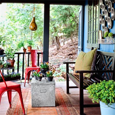 a porch with pie-tins on the wall, a bench, red metal chairs and a gourd birdhouse