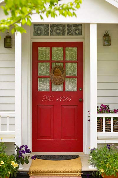 red front door with stick-on house numbers