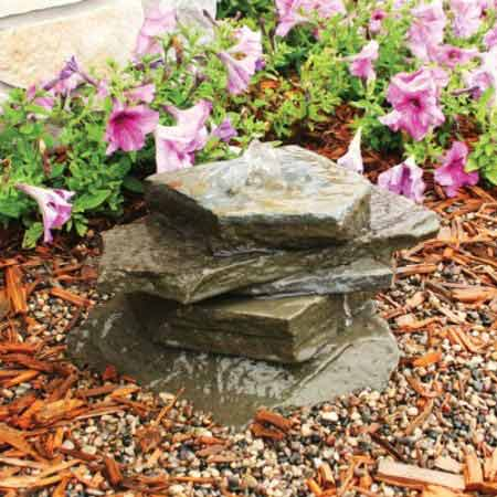 A stack of blue stone pavers in a garden