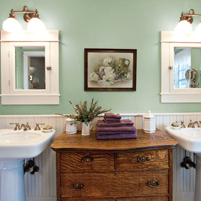green master bath with antique oak dresser and two pedestal sinks
