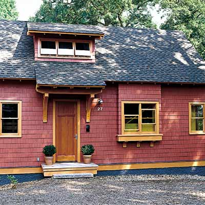 Craftsman-style cottage with red shingles and yellow trim