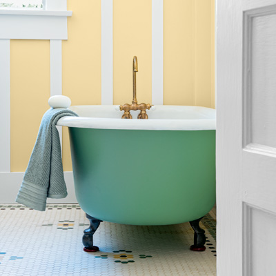 bungalow house bath with old tub painted to match green accents in hex-tile floor