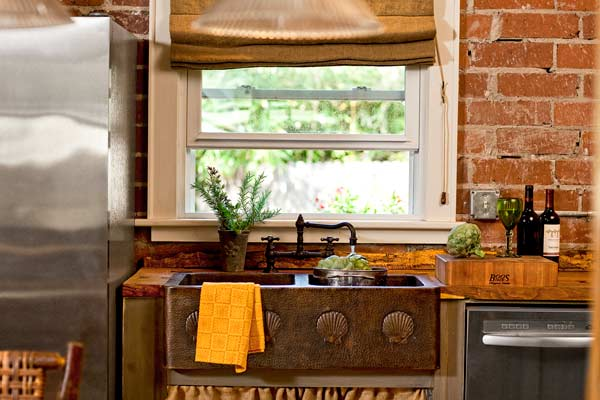 rustic copper farm sink, brick wall, live-oak countertops in open kitchen in cottage whole house remodel