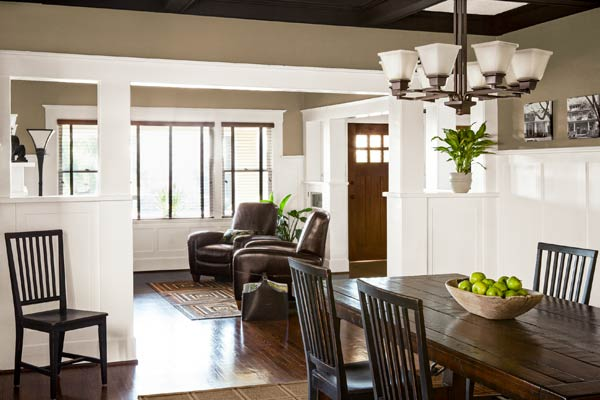 open floor plan with entry, living room and dining room of remodeled Craftsman house with built-in bookcases and wainscoting