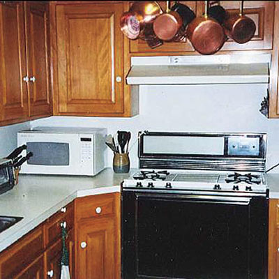 Dingy 1960s kitchen with wood cabinets