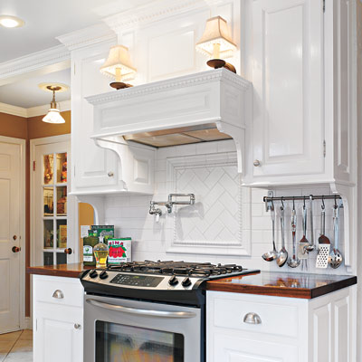 cooking area with mantel, sconces, and dentil molding