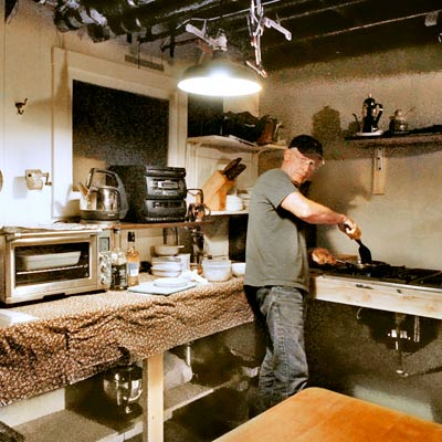 homeowner Don Post cooking in temporary basement kitchen during kitchen remodel