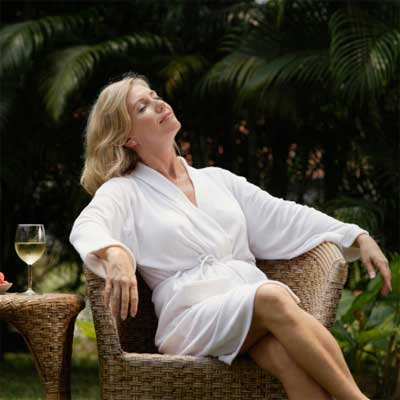 women lounging in chair with glass of wine for 23 Ways to Turn Your Home Into a Staycation Resort