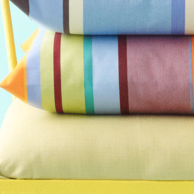 pink, red, white, green, yellow, blue and orange-striped pillow