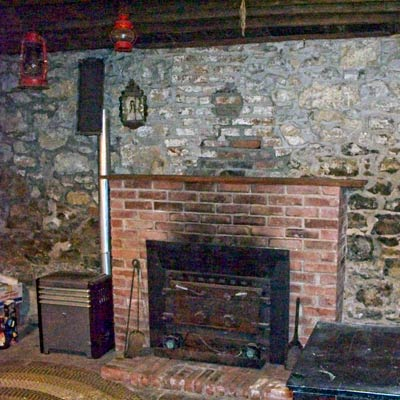 kitchen with original stone walls, exposed wood ceiling beams and fireplace in save this old house lexington, missouri greek revival